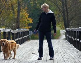 woman walking dog on bridge
