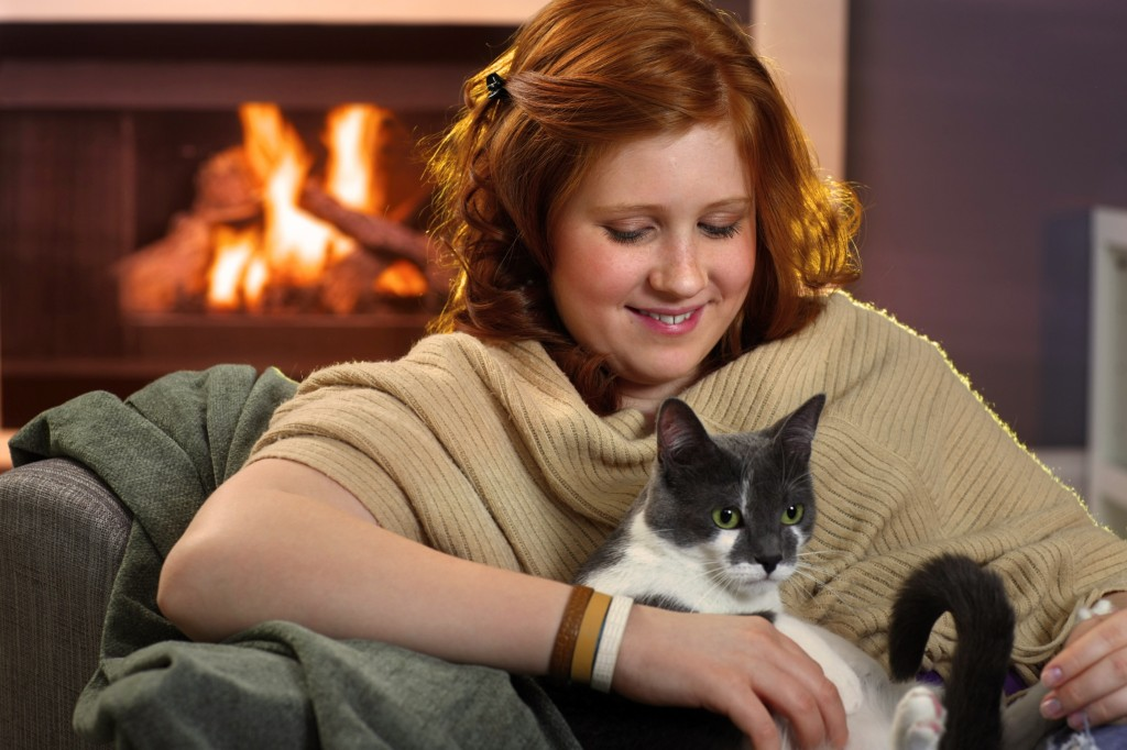Smiling teenage girl loving her cat at home